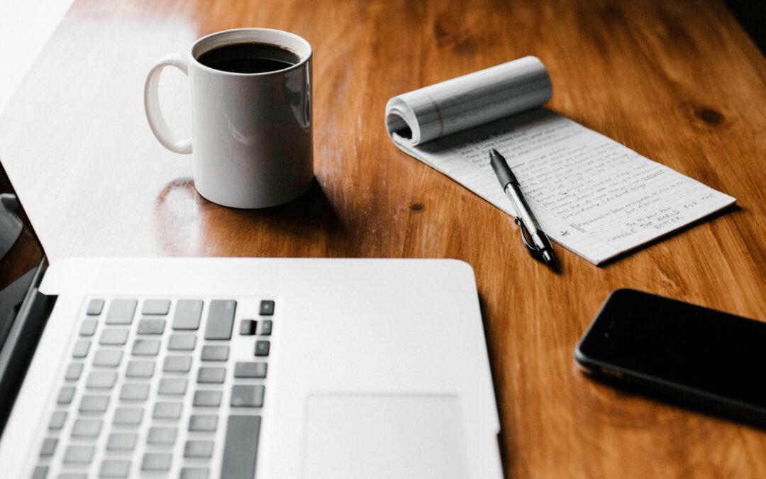 Tisch mit Laptop, Kaffeetasse, Notizblock und Smartphone