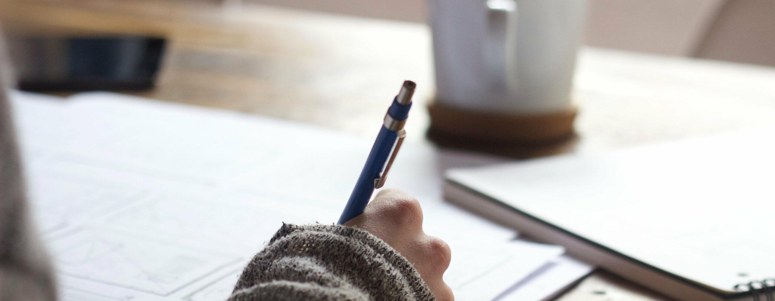 Hand hält Stift und schreibt auf Papier