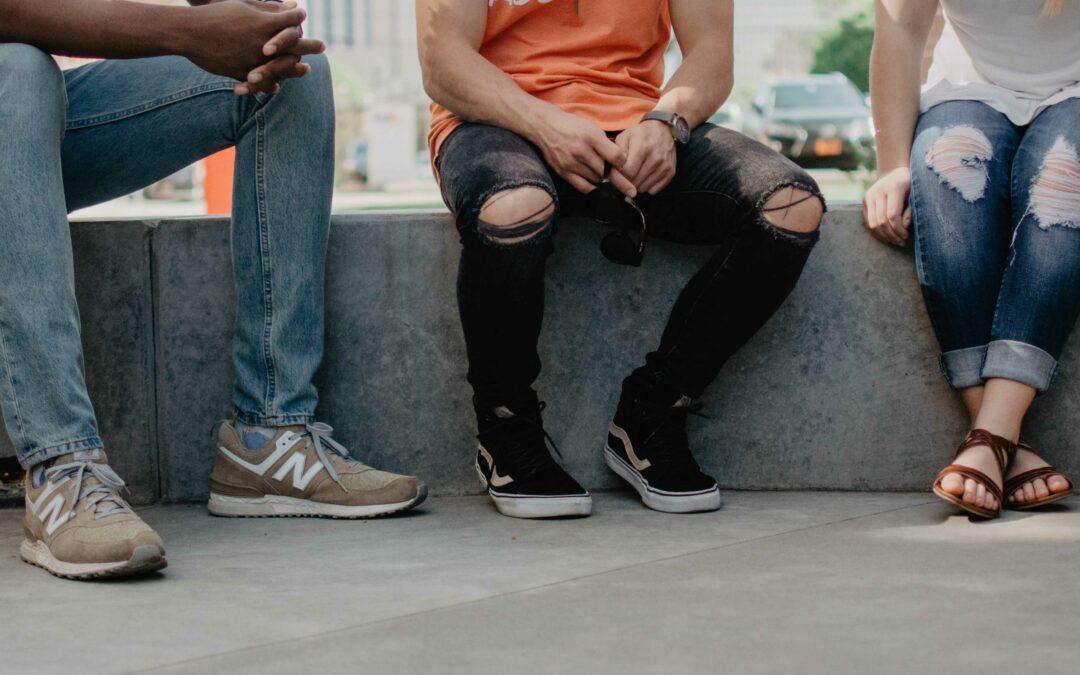 Vier Personen sitzen auf einer Steintreppe, der Ausschnitt zeigt nur die Beine der Personen