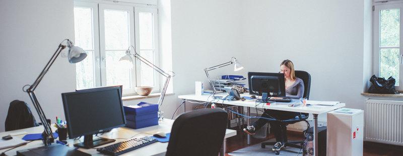 Mitarbeiterin sitzt an Schreibtisch in der Agentur