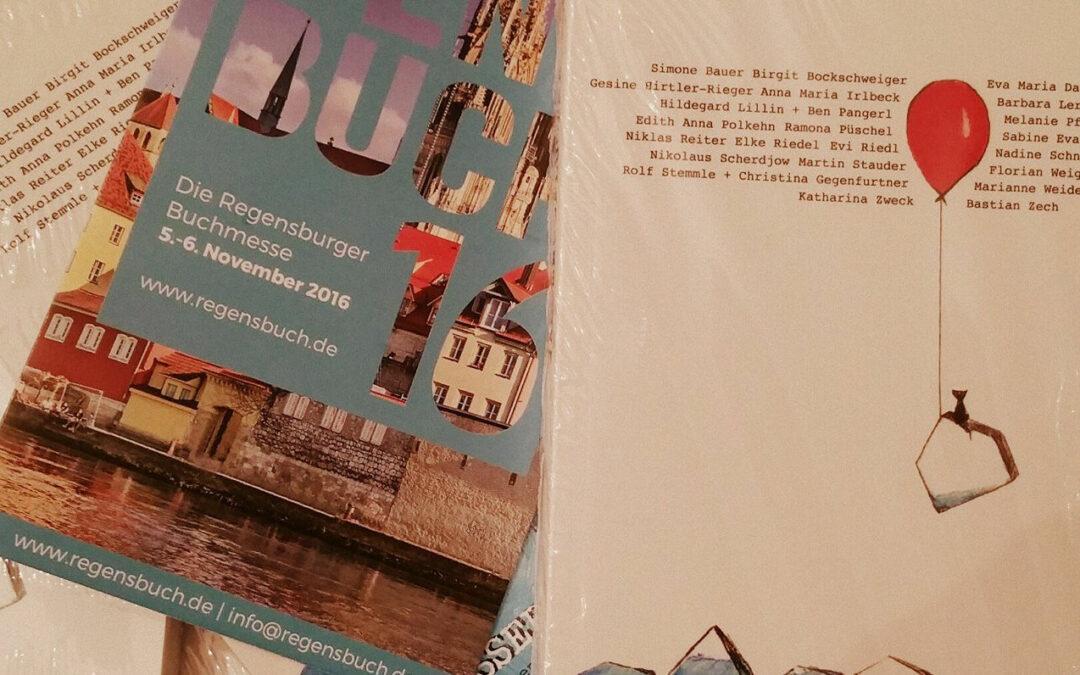 Buch Wassergeflüster und Flyer der Regensburger Buchmesse zu sehen
