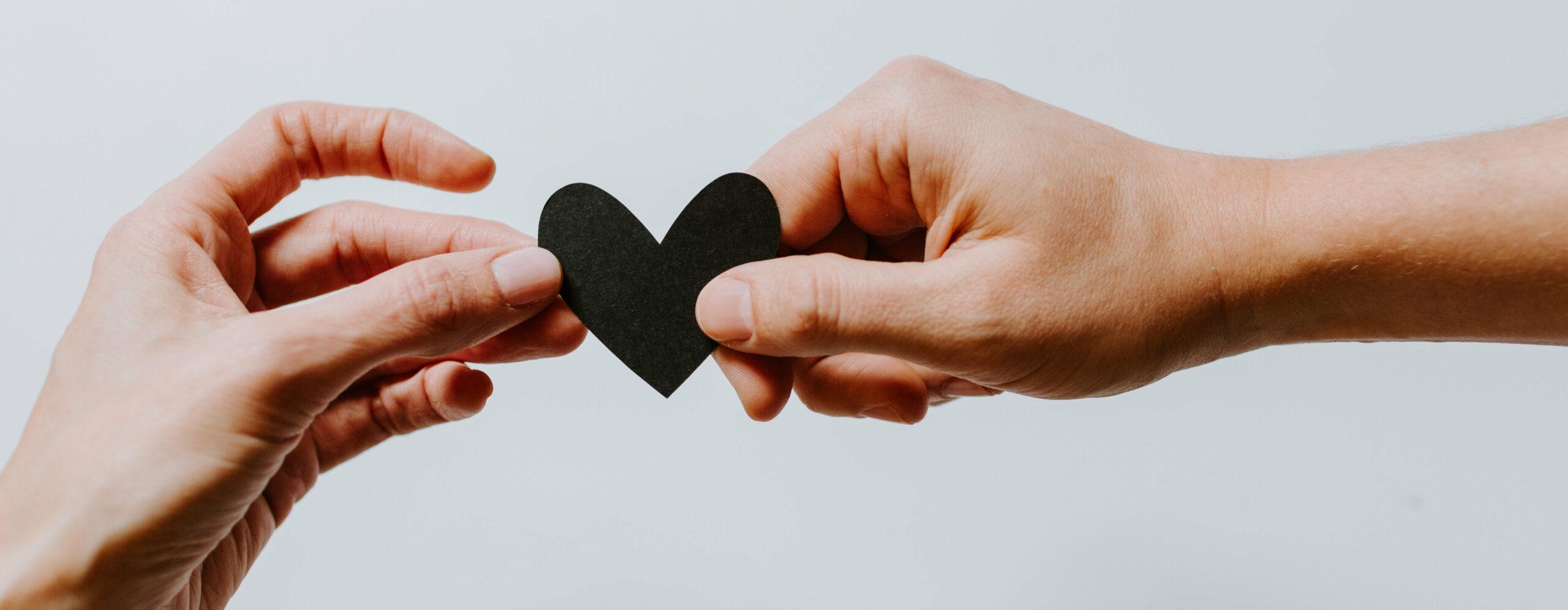 Zwei Hände, die beide ein Herz festhalten