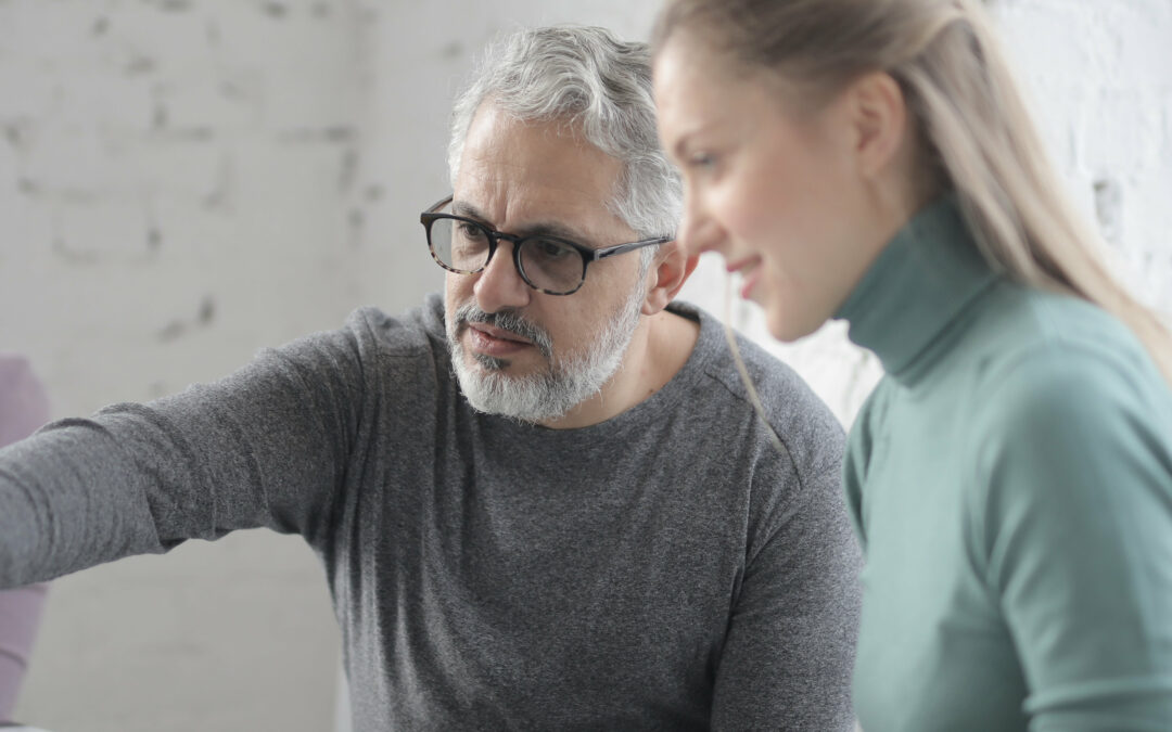 Mann erklärt Frau etwas am Laptop