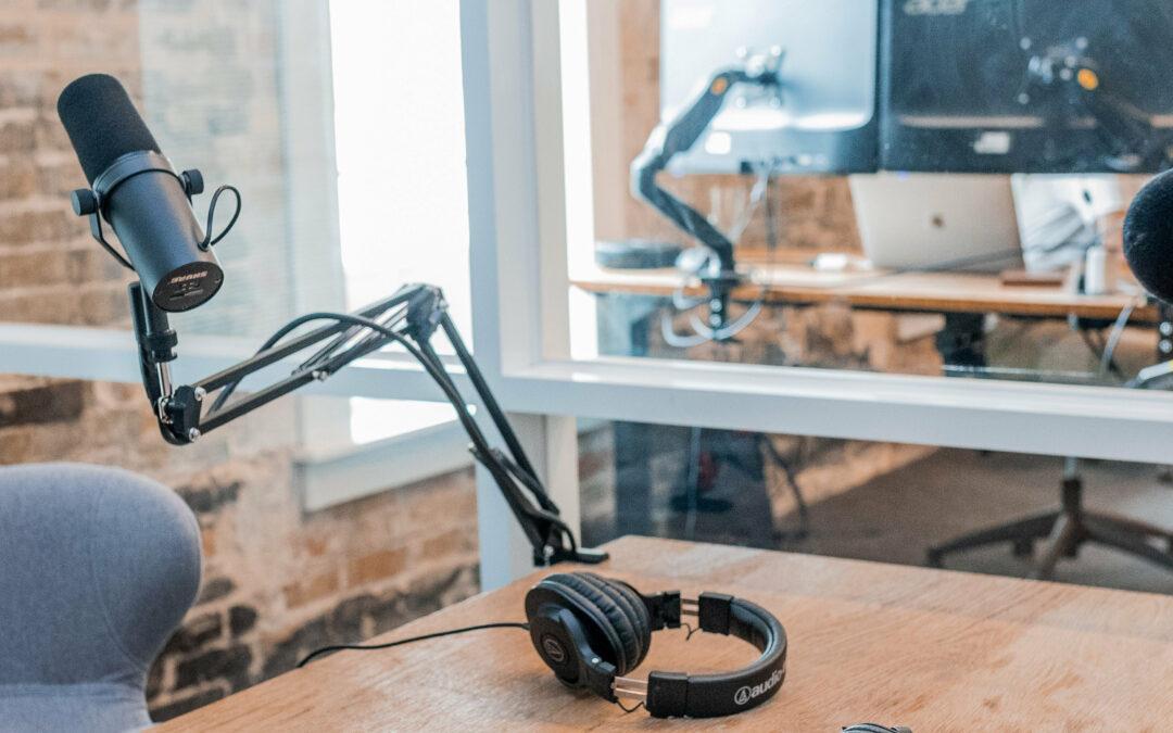 Zwei Mikrophone und Kopfhörer liegen auf einem leeren Tisch