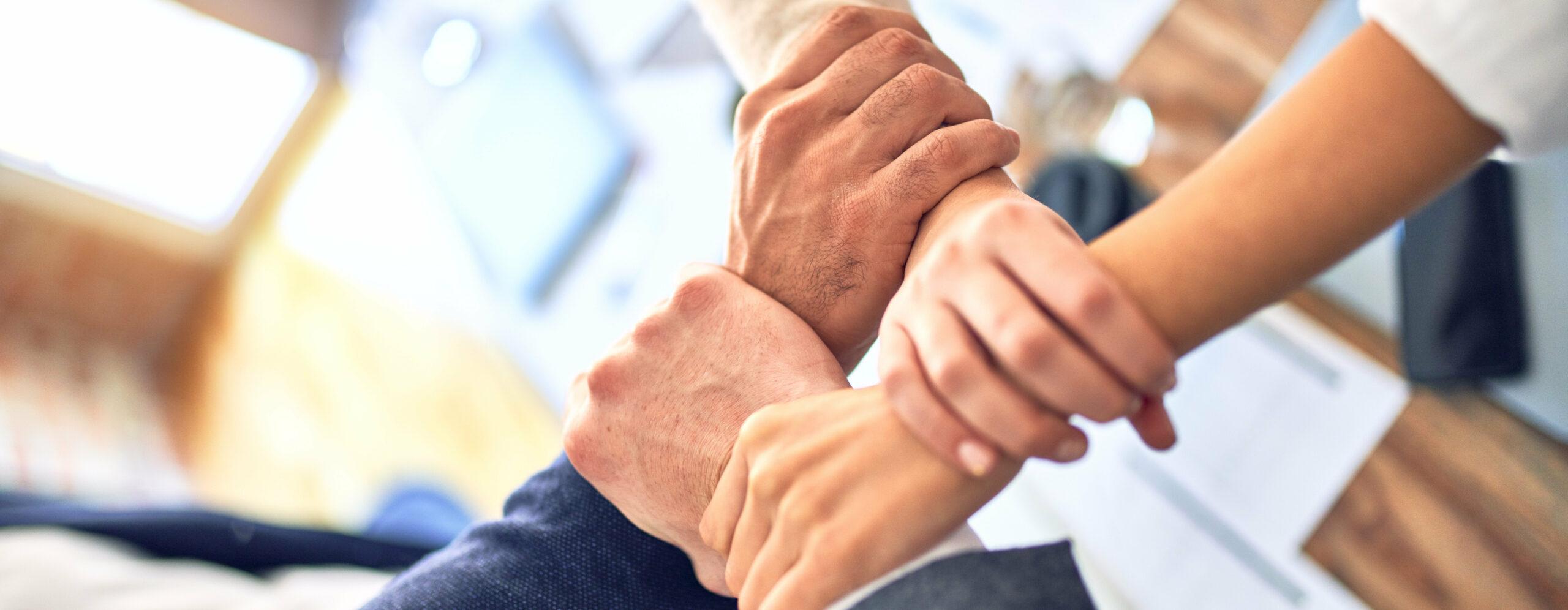 Vier Hände halten sich an den Handgelenken