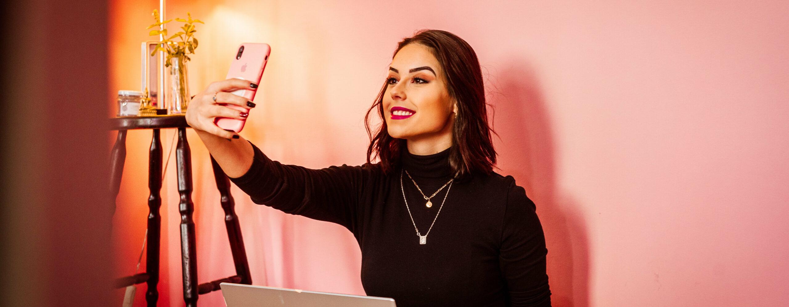 Frau hält ein Smartphone und macht ein Selfie