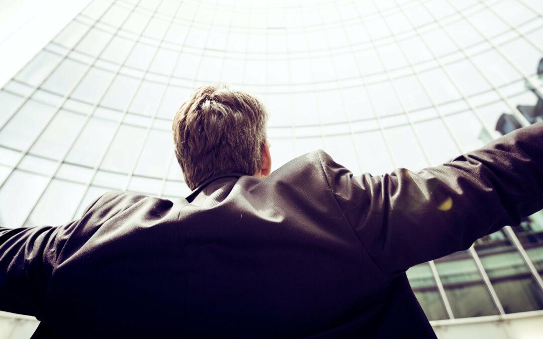 Mann mit ausgebreiteten Armen blickt Richtung Himmel