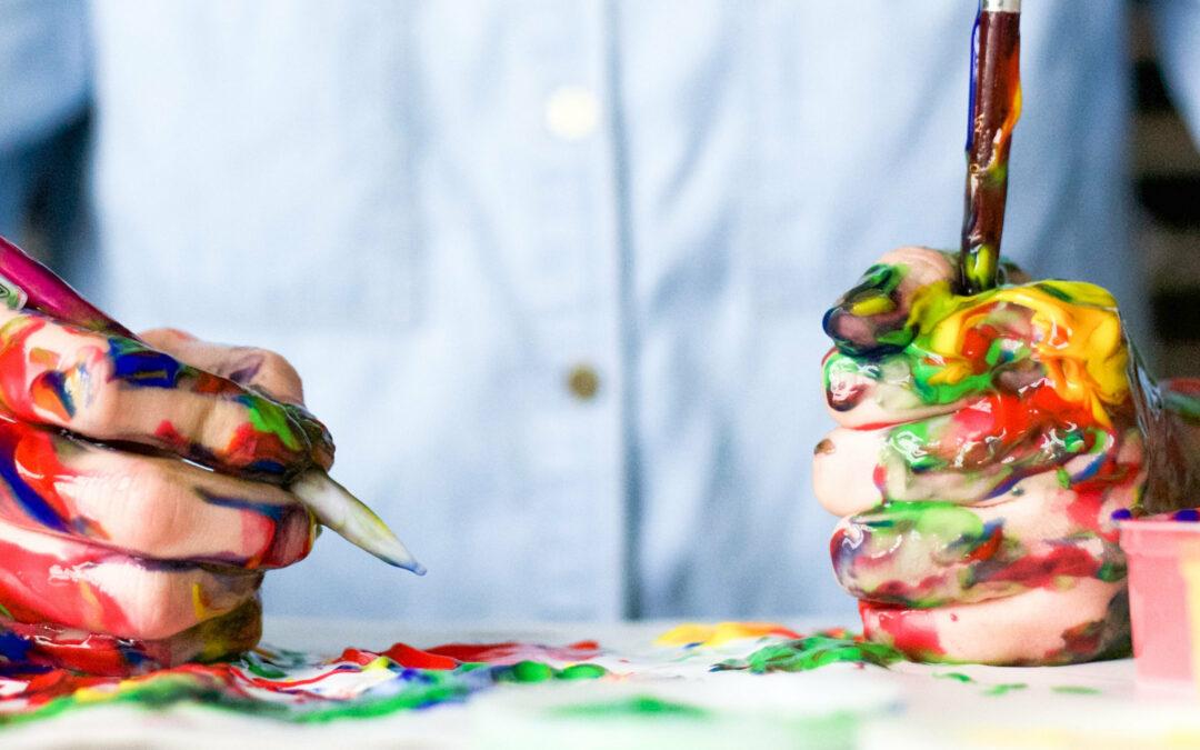 Mann mit farbverschmierten Händen, einem Pinsel und einem Kugelschreiber