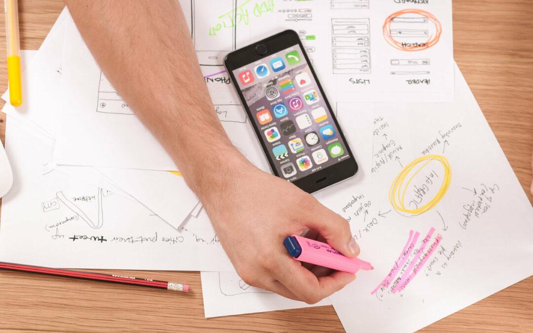 Vor einer Person liegen viele Unterlagen und ein Smartphone