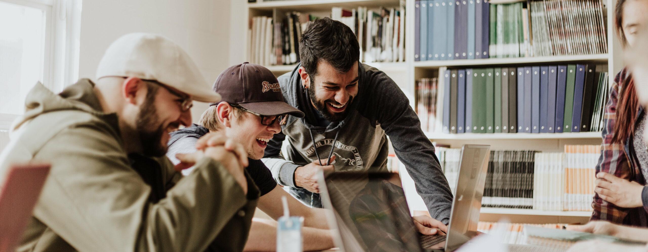 Drei Männer beugen sich über einen Laptop und lachen