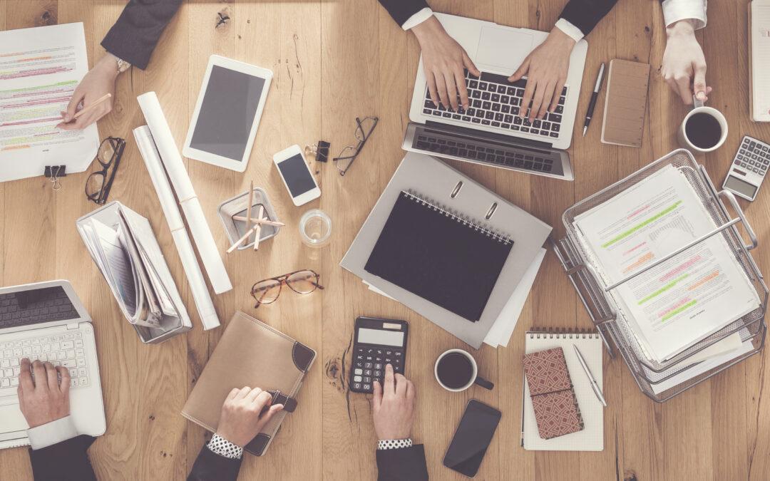 Schreibtisch mit Laptops, Smartphones und Unterlagen