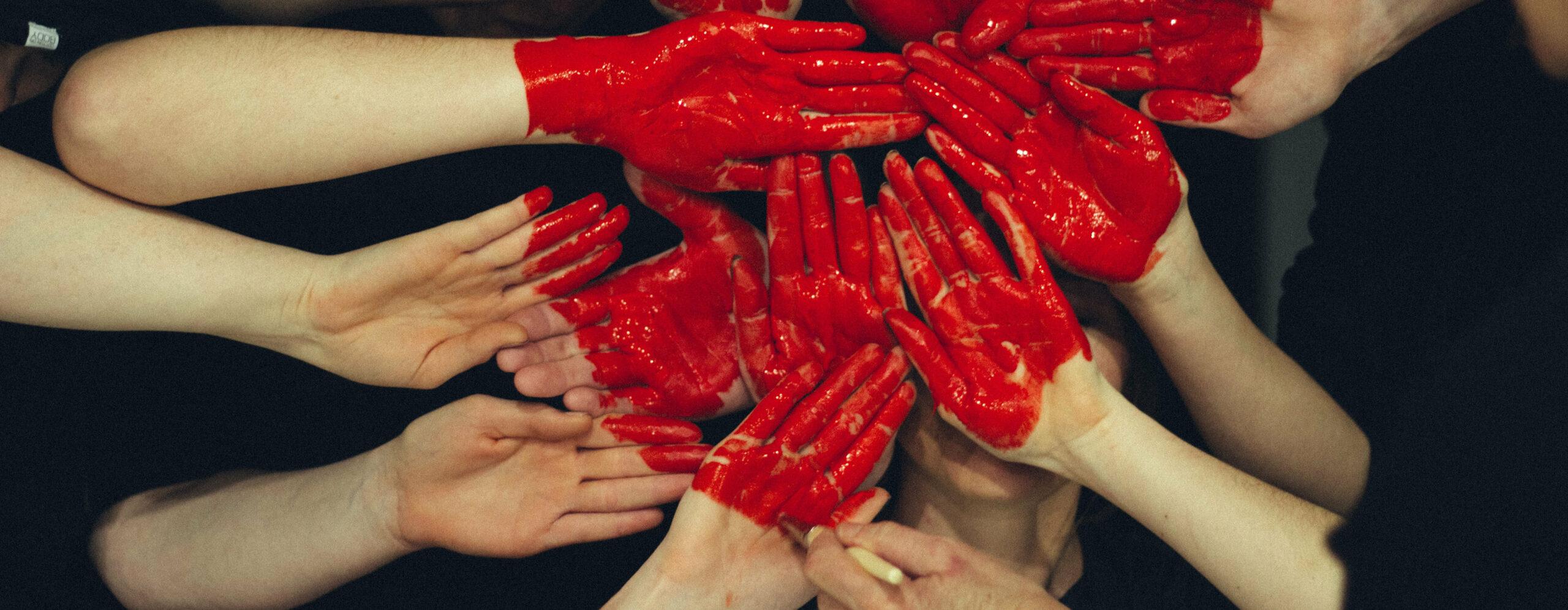 Viele Handflächen mit roter Farbe bedeckt