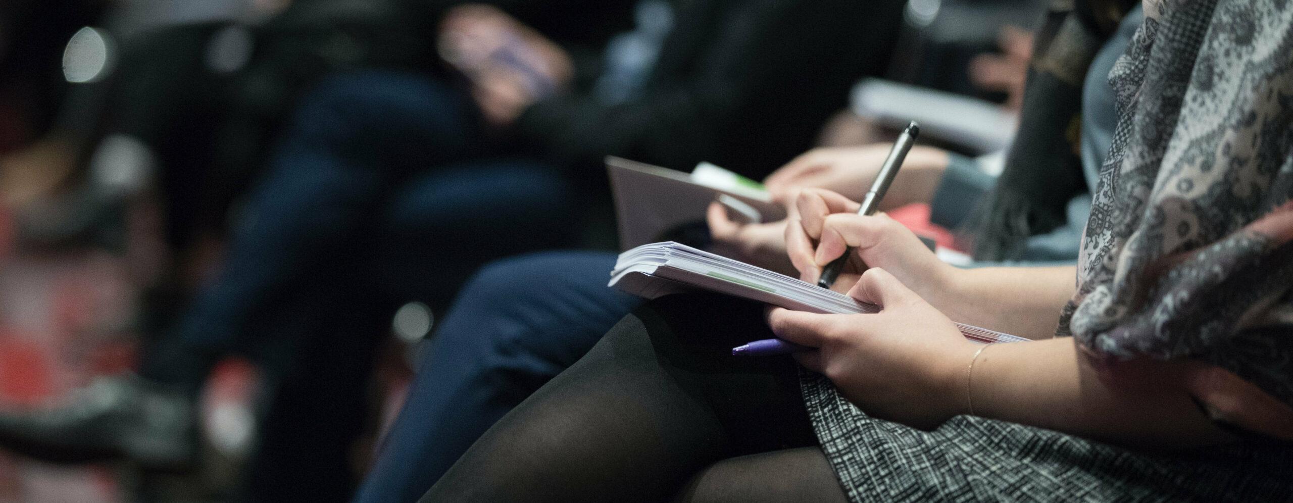 Personen sitzen in einer Reihe und schreiben auf Notizblöcken