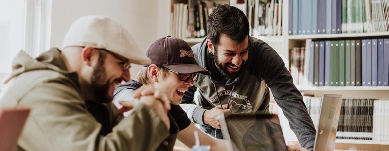 Männer am PC lachen und zeigen drauf