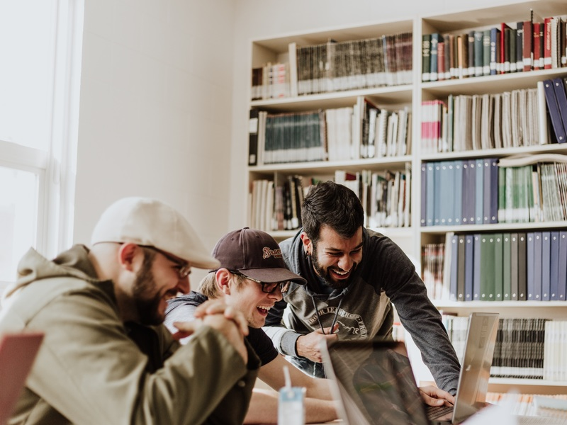 Drei junge Männer schauen lachend gemeinsam in einen Laptop-Monitor