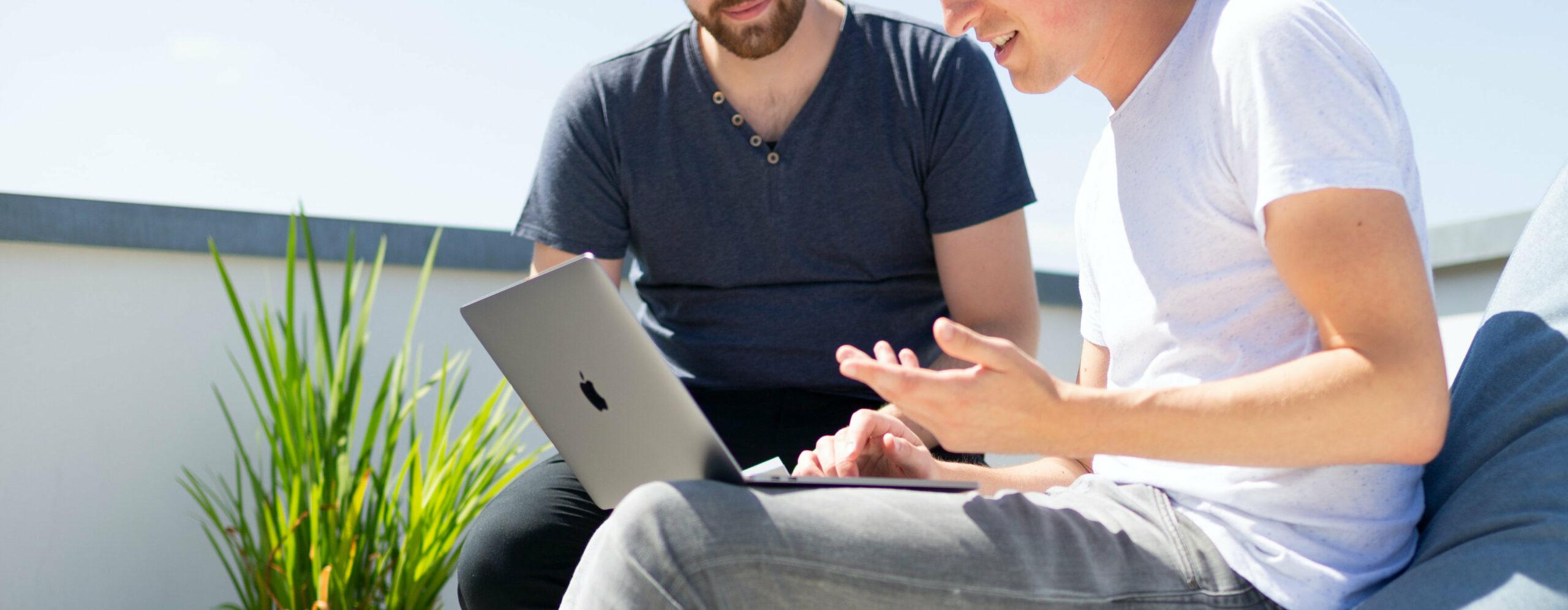 Zwei Männer sitzen mit Laptops auf Terrasse und arbeiten