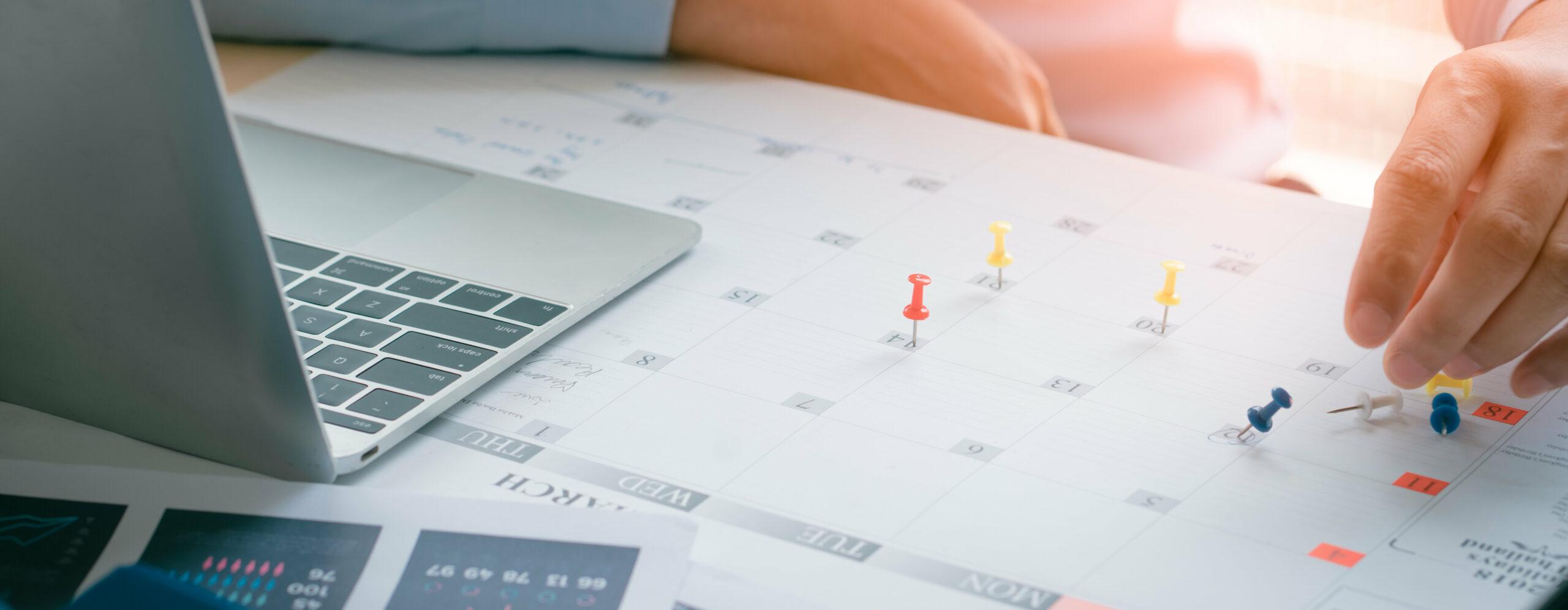 Mann sitzt an Laptop und arbeitet an einem Kalender