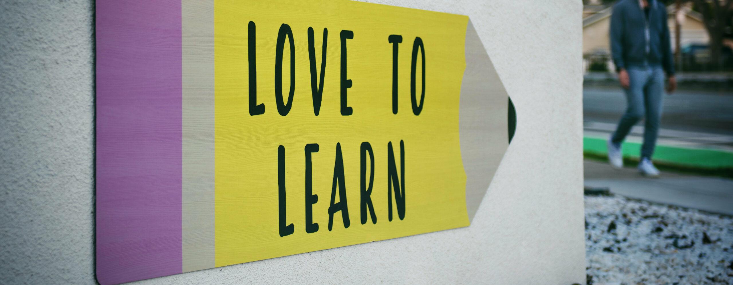 """Schild eines Bleistifts mit der Aufschrift """"Love to learn"""""""