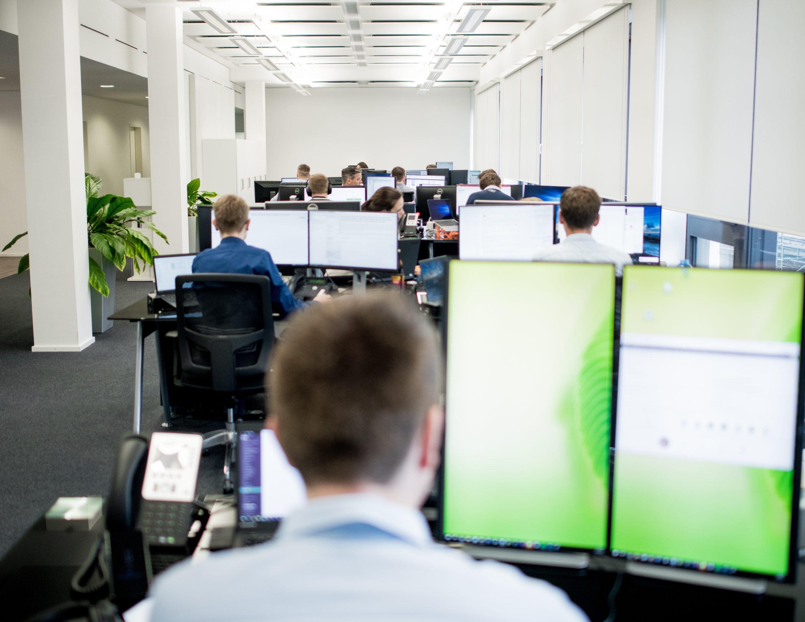 Großraumbüro mit Entwickler-Bildschirmen
