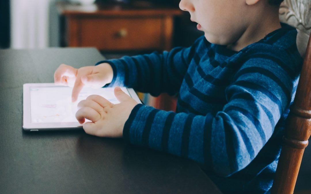 Kind sitzt vor Tablet