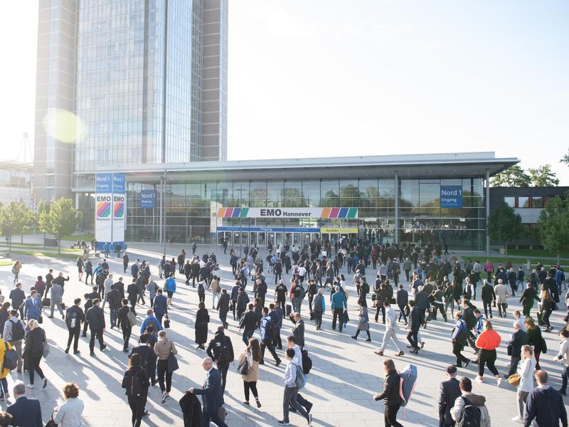 Blick auf den Eingang des Messegeländes der EMO Hannover mit vielen umhergehenden Menschen
