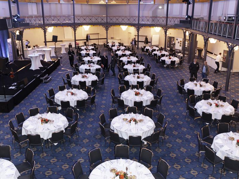 Blick von oben in den Festsaal mit gedeckten Tischreihen