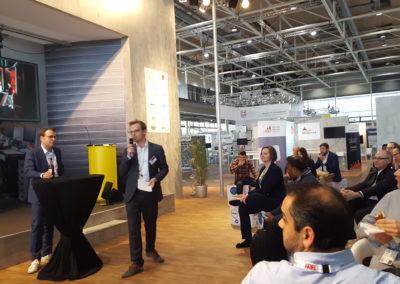 Publikum sieht auf Bühne des Industrial Forums, wo gerade ein Speaker vorgestellt wird