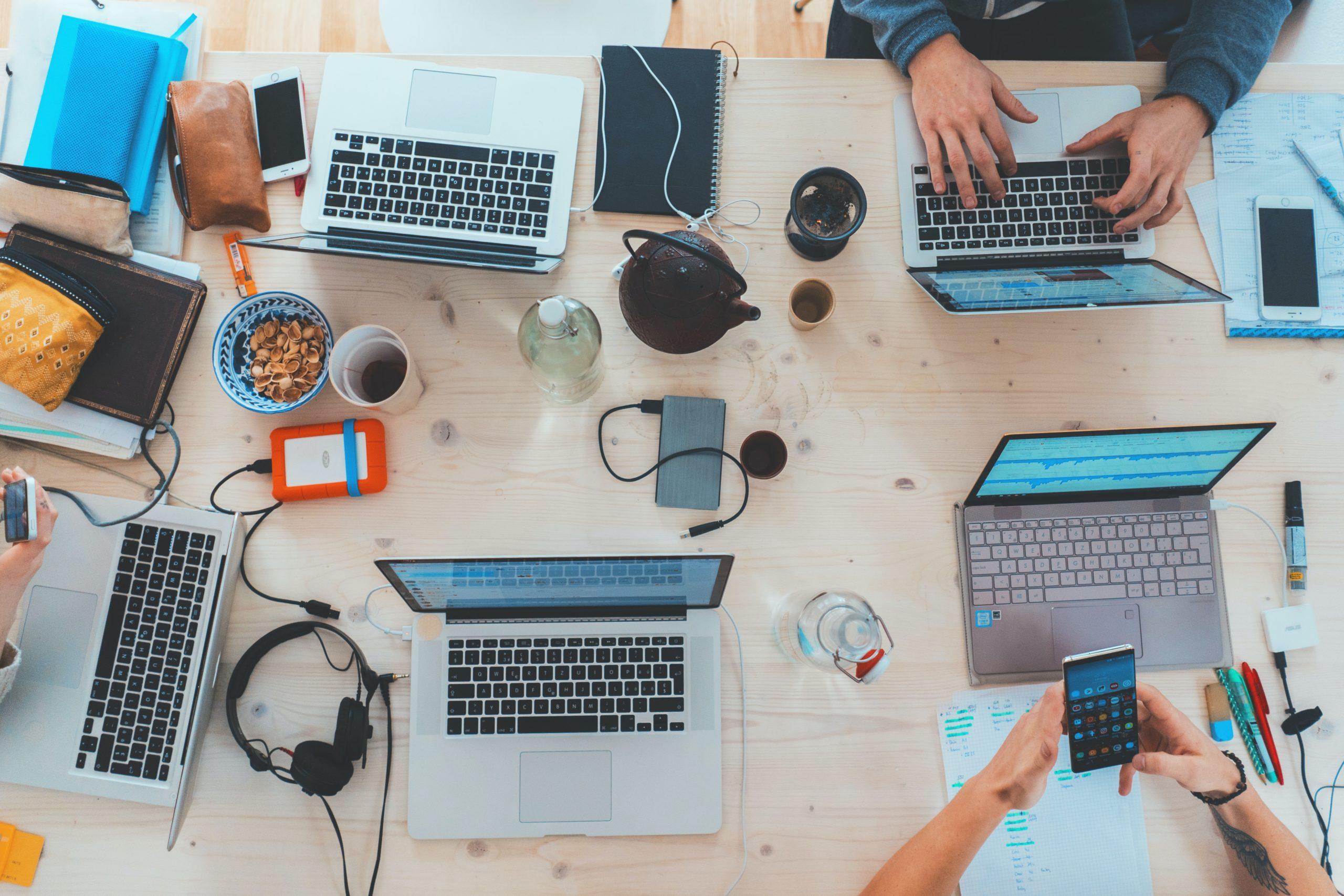 Mitarbeiter sitzen mit Laptops und Handys zusammen an einem Tisch