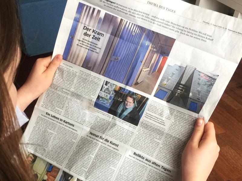 Frau hält Zeitung, aufgeschlagen ist ein Artikel über MyPlace-SelfStorage