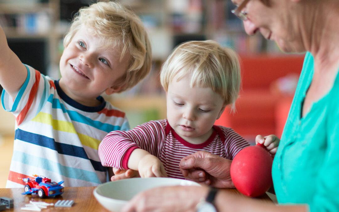 Frau mit zwei Kindern spielt am Tisch