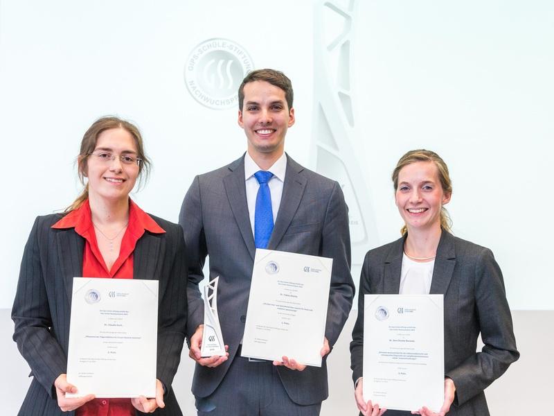 Die drei Gewinner:innen des Nachwuchspreises halten lächelnd ihre Urkunden in die Kamera