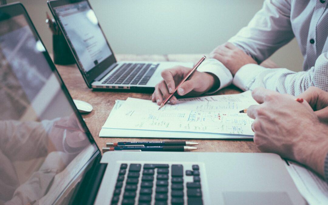 Zwei Männer sitzen am Tisch mit ihren Laptops, Stift und Papier