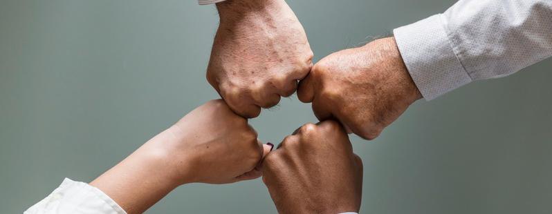 Vier Fäuste stoßen gemeinsam zum Teamwork aneinander