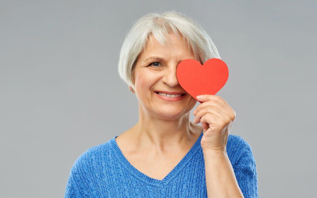 Ältere Frau hält sich ein Papierherz vors Auge