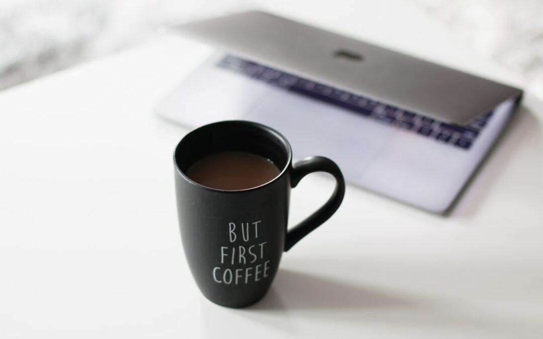 Kaffeetasse steht vor zugeklappten Laptop