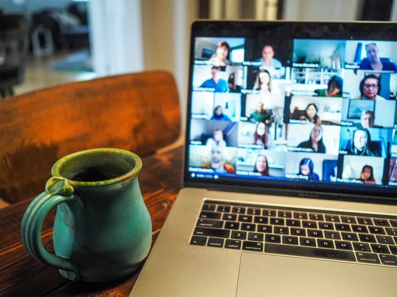 Eine Tasse und ein Kaptop, auf dem eine digitale Konferenz stattfindet