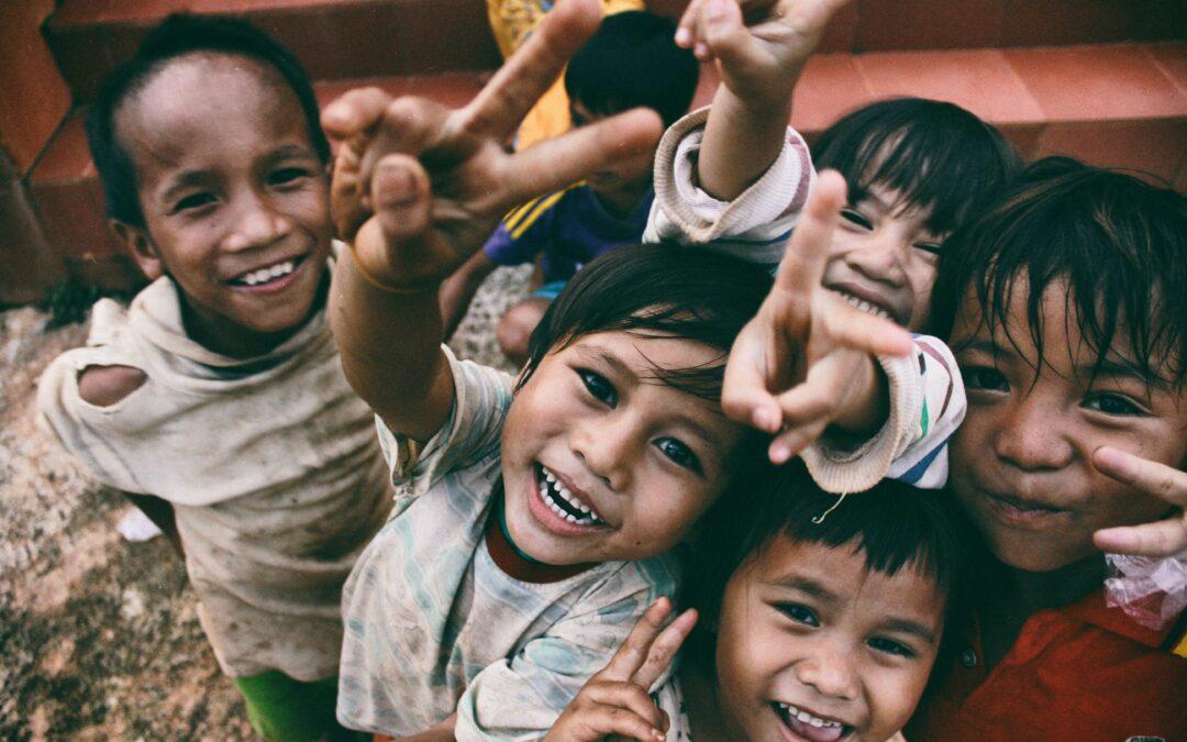 Kinder lachen in die Kamera und machen das Peace-Zeichen