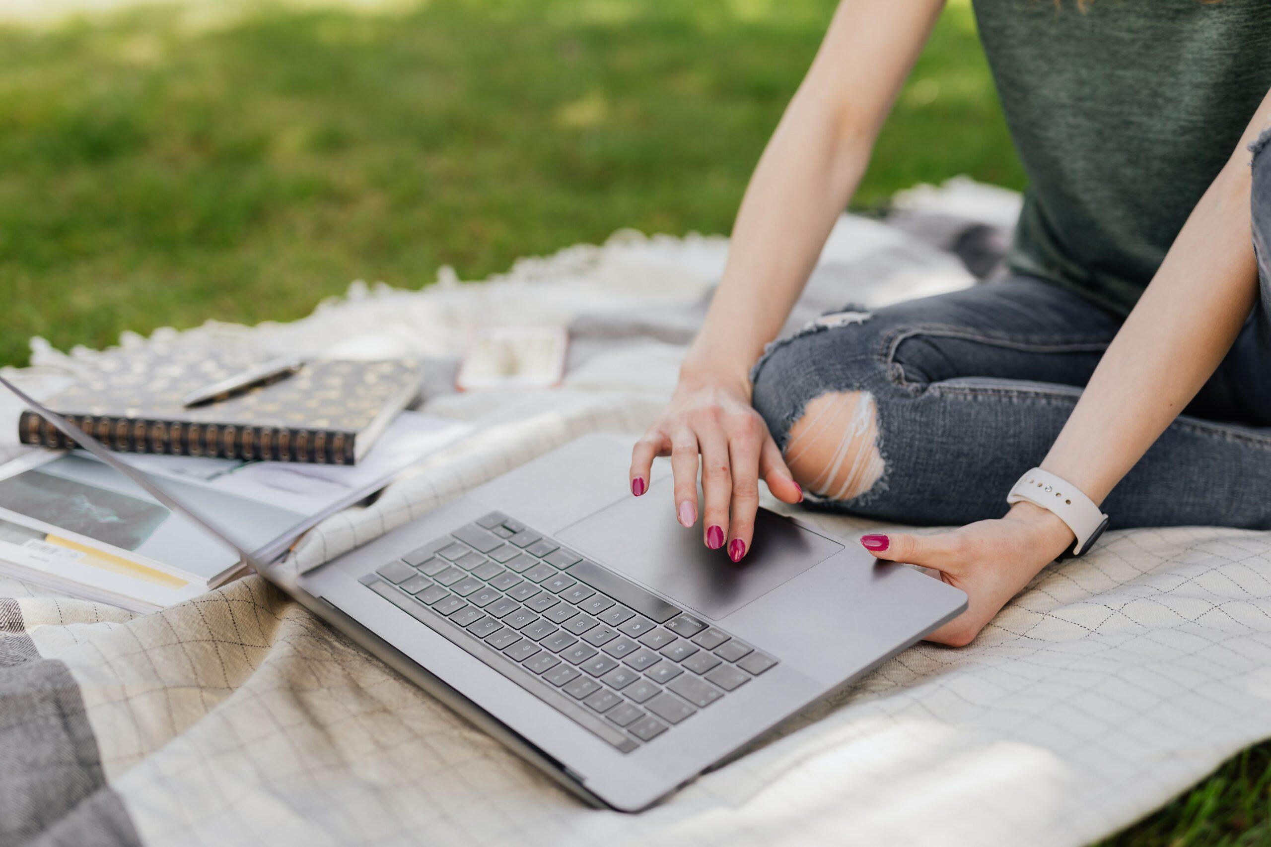 Frau sitzt im Park auf einer Decke mit ihrem Laptop