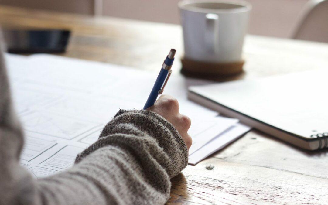 Mensch sitzt am Tisch und schreibt